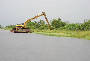 An excavator undertaking works at EDWC to clear waterways and heighten the embankment