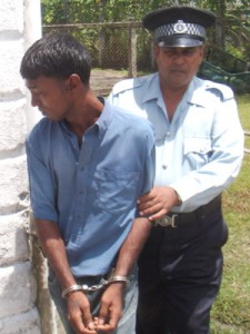 Hamraj Rambachan is led away by Police after being formally charged with murdering Zeeburg widow Rajpattie Jagroop.