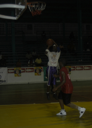 I GOT THIS!!! President College's, Willon Cameron pulls up for a jumper after faking Saints' Mickhail Husbands (forefront) last night at the Cliff Anderson Sports Hall.