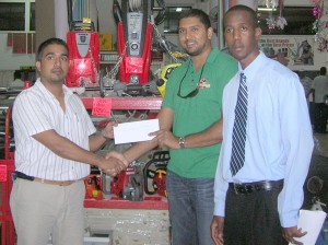 Moen Gafoor receives the check from Mr. Bhaichandeen (left) at the Emporium Hardware Store in the presence of his colleague, Leon Belony.