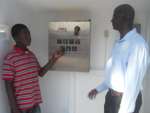 GWI sanitation Manager, Rensfore Joseph, gives direction to the Sewerage pump station attendant