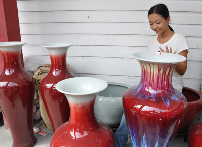 Alice Cao sits among a set of large porcelain vases.